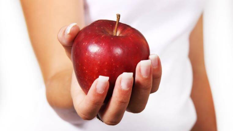 lady at an office holding a heathly red apple