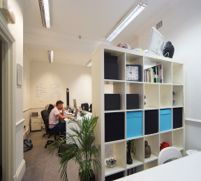 Five person office with tall cabinet with shelves